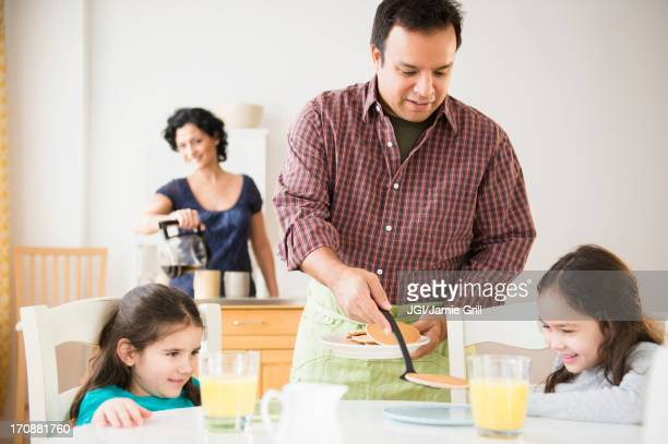 Father serving daughters breakfast at table