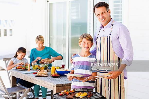 Father Serving Food To Son By Barbecue At Porch