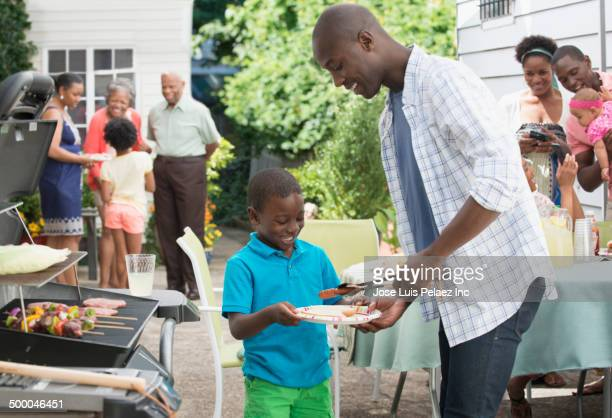 Father serving son at barbecue