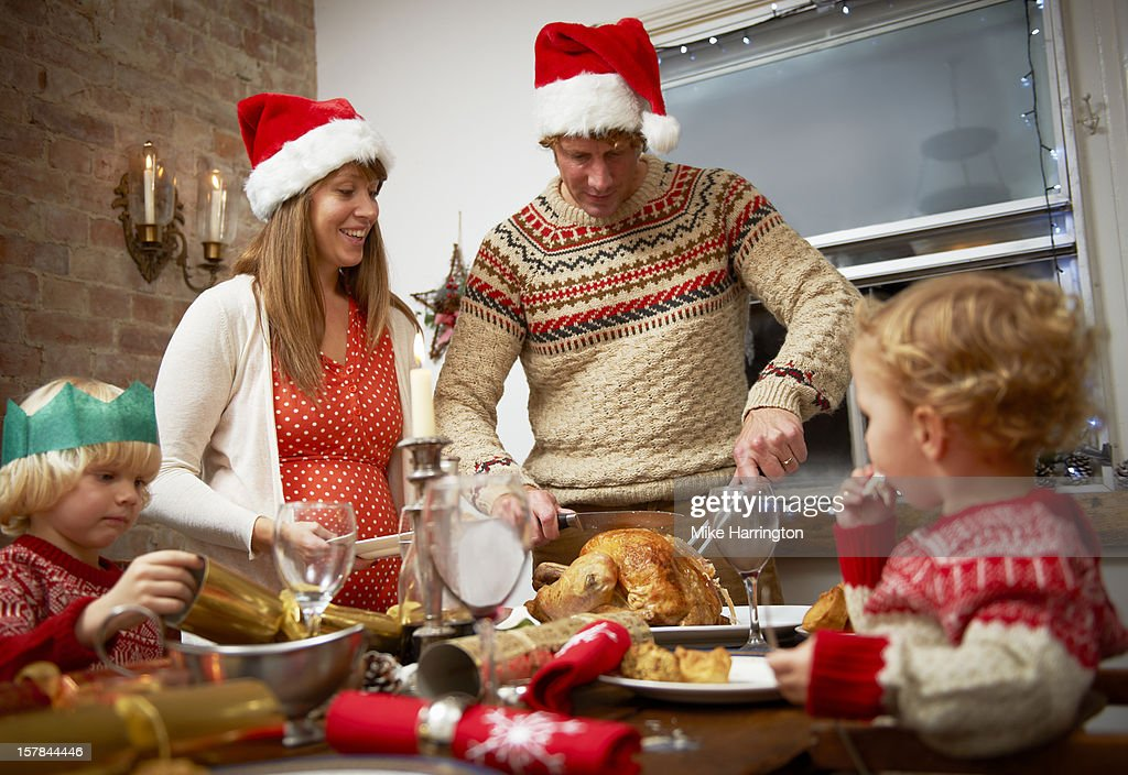 Father serving up Christmas dinner to family. : Stock Photo
