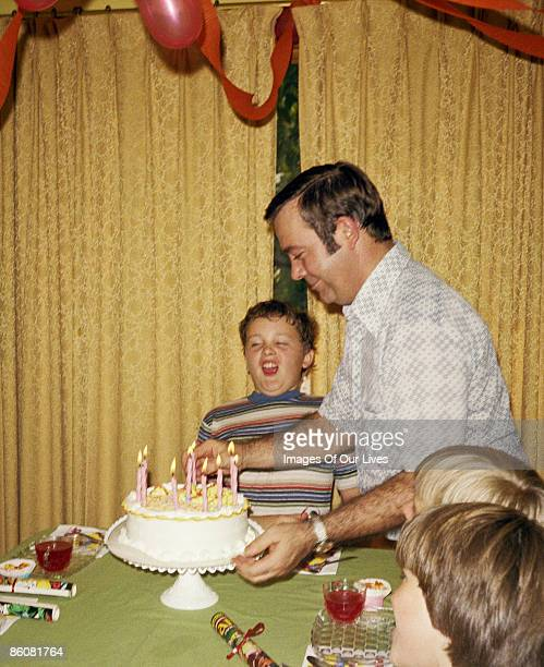 Father setting down birthday cake for son at party