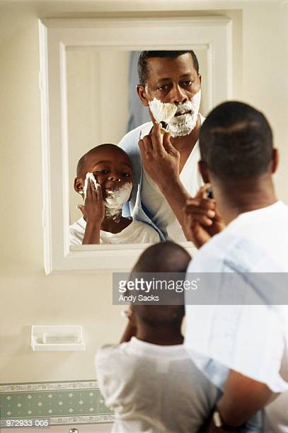 Father shaving at mirror, son (6-8) putting on shaving foam
