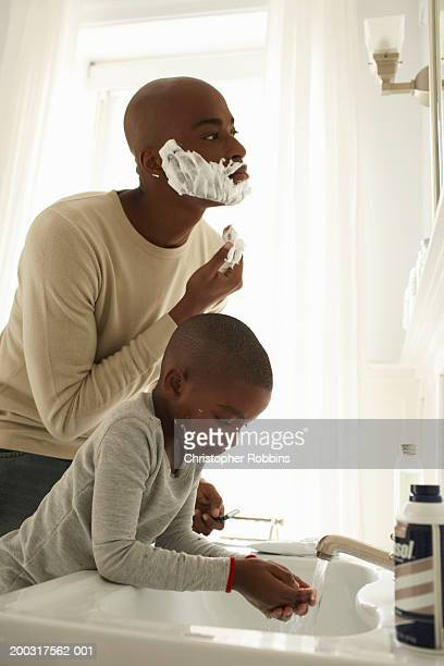 Father shaving by son (5-7) using tap of sink