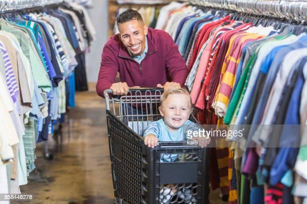 Father shopping, pushing son in cart