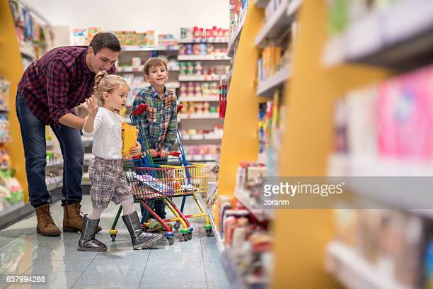 Father shopping with children at supermarket