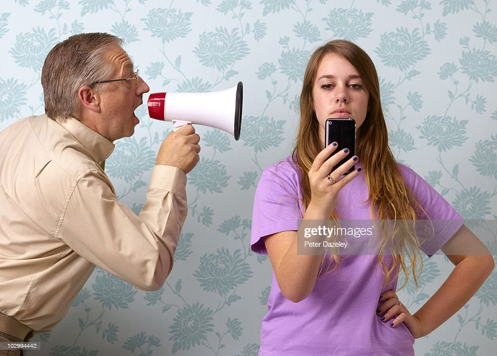 Father shouting at daughter texting : Stock Photo