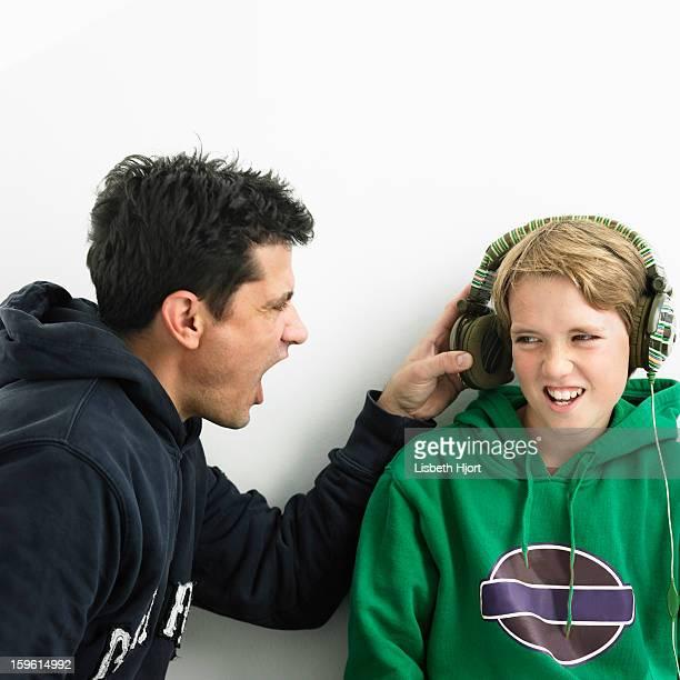 Father shouting into boys earphones