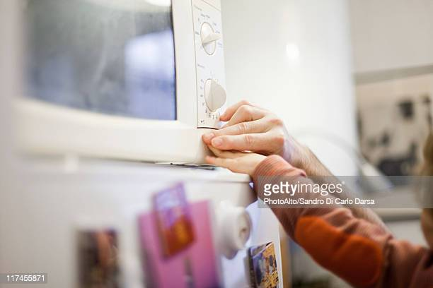 Father showing child how to use microwave, cropped view of hands pushing button