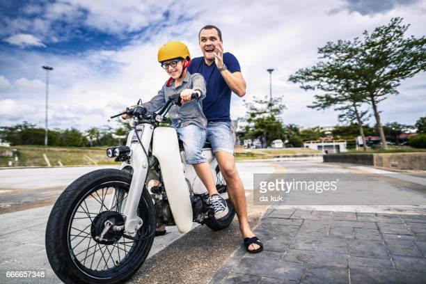 Father showing his son how to ride custom bike