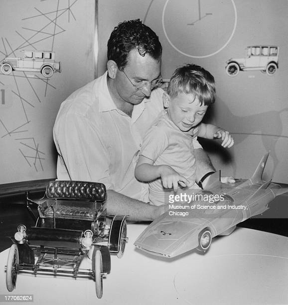 A father showing his son models of the first car produced by General Motors as well as a model of a concept car which was part of the Motorama...