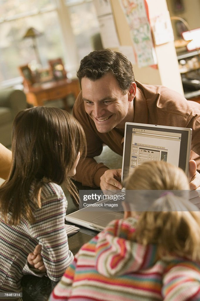 Father showing laptop to daughters : Stock Photo