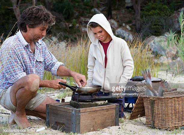 Father showing son (9-11) how to cook fish, outdoors