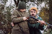 handsome Father showing son how to load gun for hunt