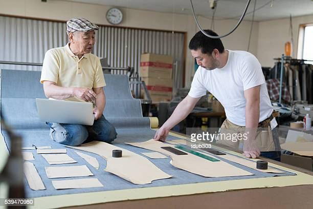 Father showing son how to make denim jeans by hand