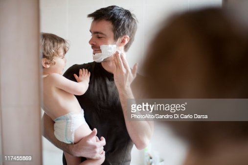 Father showing toddler son how to apply shaving cream : Stock Photo