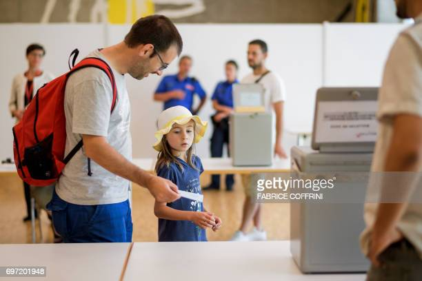 A father shows his ballot to his daughter during an election concerning the cantonal membership of the commune of Moutier at a polling station in...