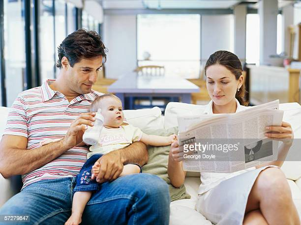 Father sitting holding his baby son and mother reading a newspaper