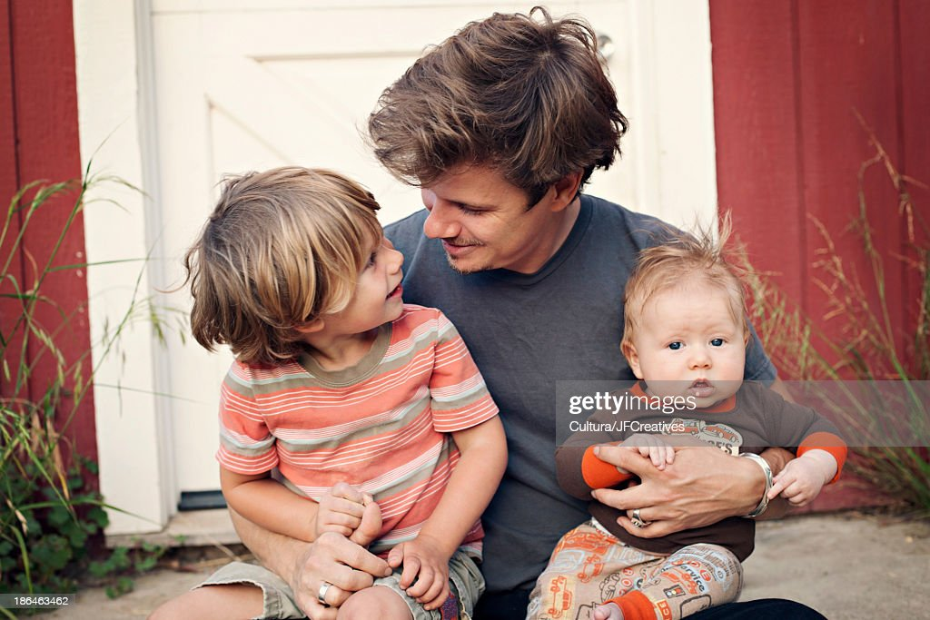 Father sitting on doorstep with children on his knee : Stock Photo
