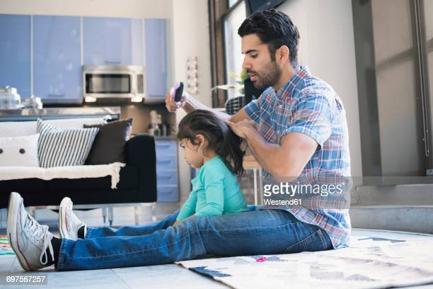Father sitting on floor doing daughters hair