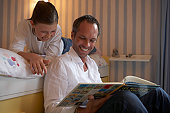Father sitting on floor reading to daughter (9-11) lying on bed