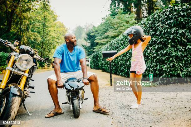Father sitting on miniature motorcycle near daughter