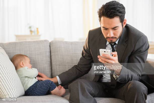 Father sitting with baby and using cell phone