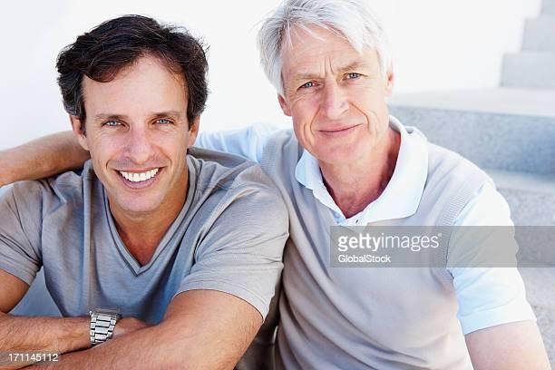 Vater mit seinem Sohn sitzen und Lächeln