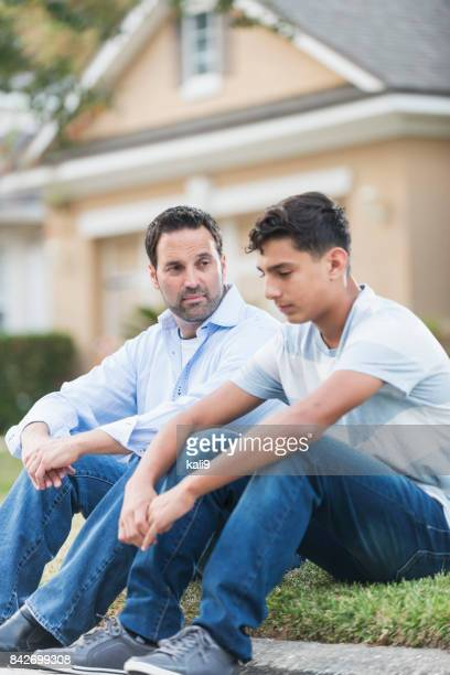 Father sitting with serious teenage boy