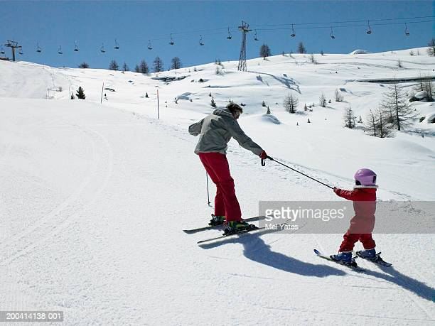 Father skiing on slope towing daughter (3-6) with ski pole, rear view