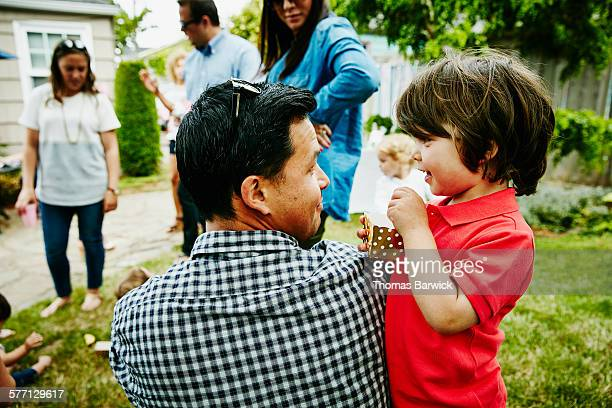 Father smiling at toddler son during party