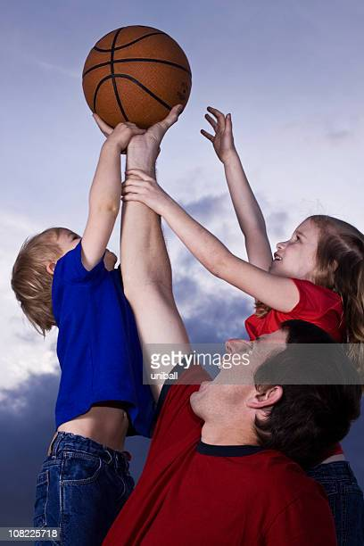 Father, son and daughter playing basketball
