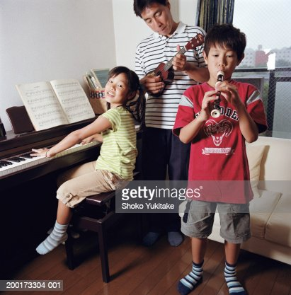 Father, son and daughter (7-9) playing musical instruments