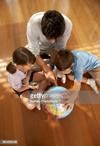 Father, son and daughter studying the word globe : Stock Photo