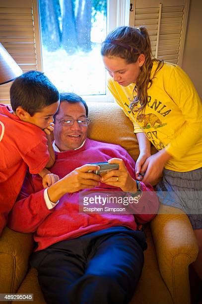 Father, son and daughter watching a cell phone