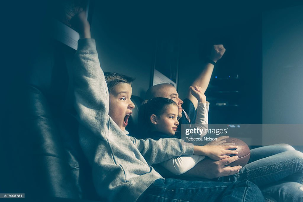 father, son and daughter watching football game : Stock Photo