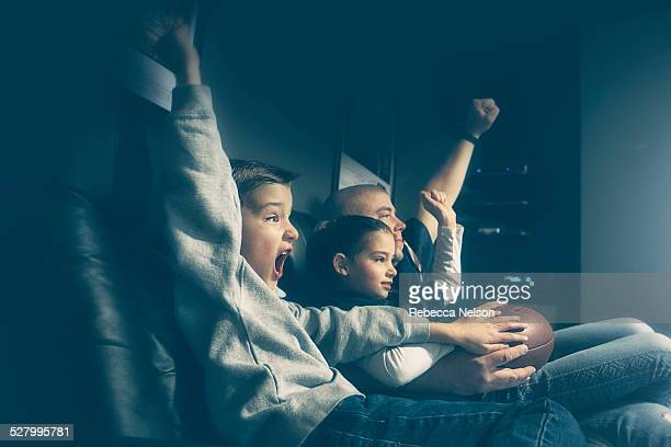 father, son and daughter watching football game