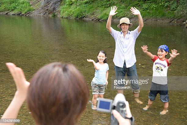 Father, son and daughter waving hands to camera