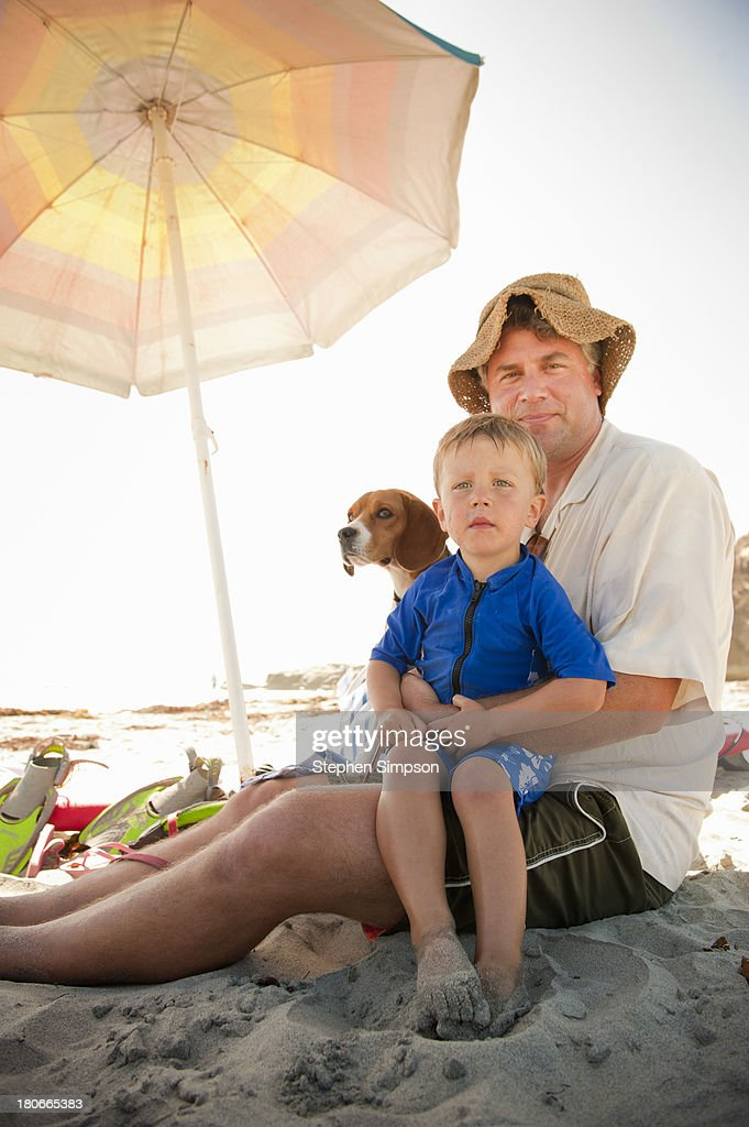 father, son and dog relax at the beach : Stock Photo