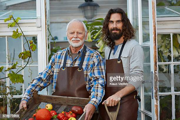 Father & son in front of greenhouse with produce