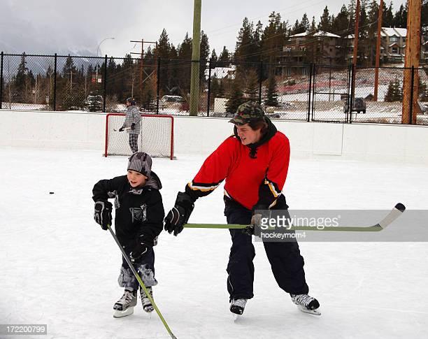 Padre e hijo jugando & hockey sobre hielo en pista al aire libre