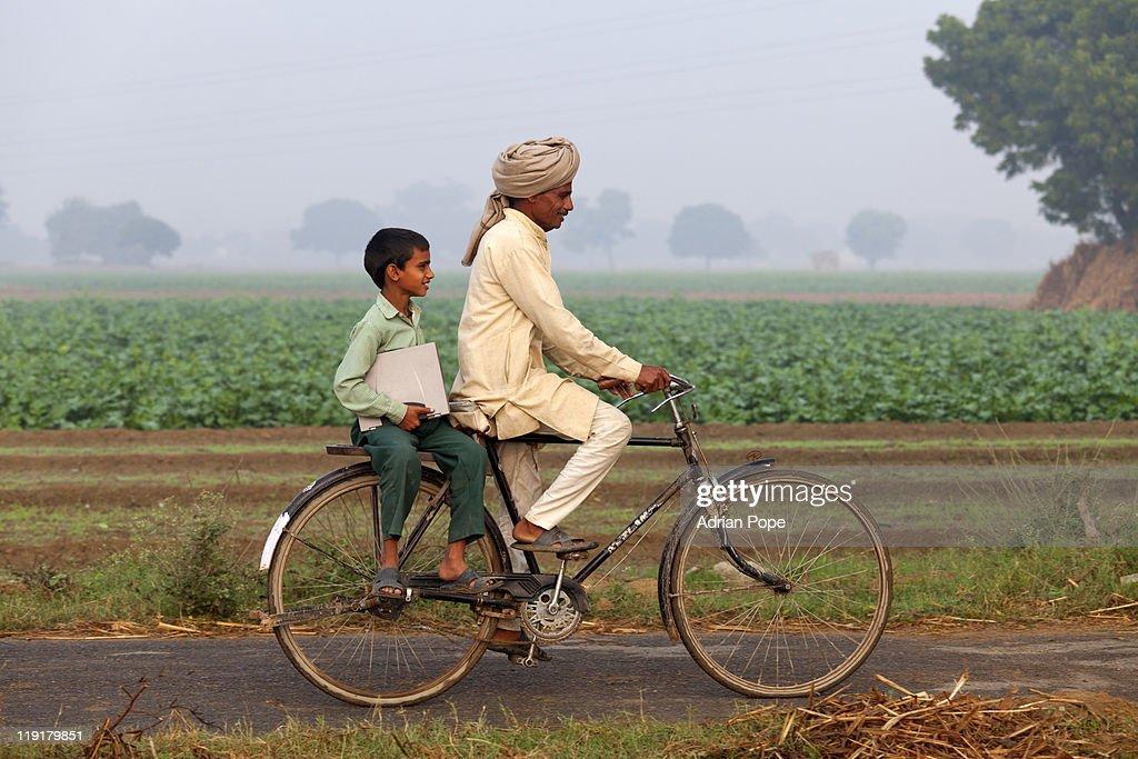 Father & son riding bike to school : Stock Photo