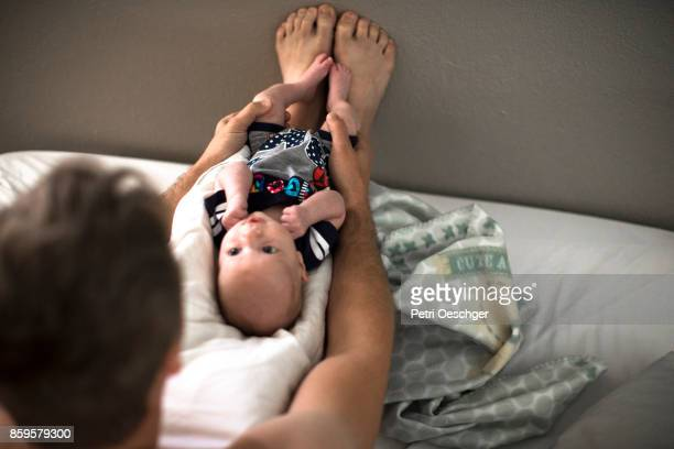 A father spends time with his baby boy at home.