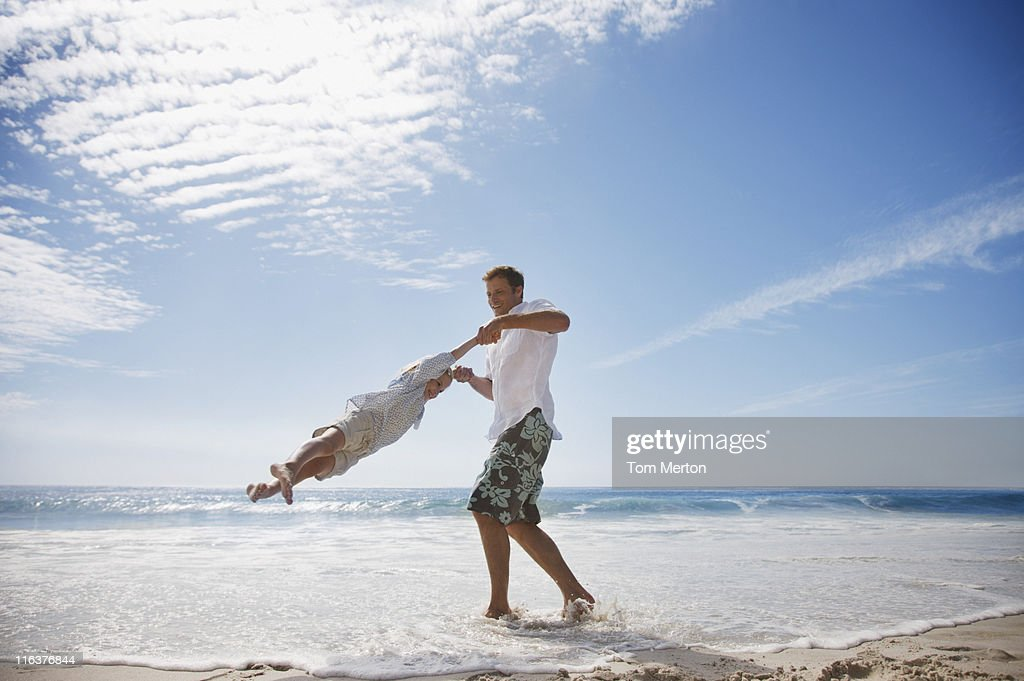 Father spinning daughter on beach : Stock Photo