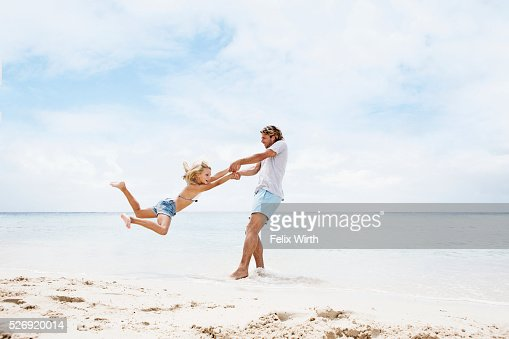 Father spinning his daughter (10-12) in air on beach : Stock-Foto