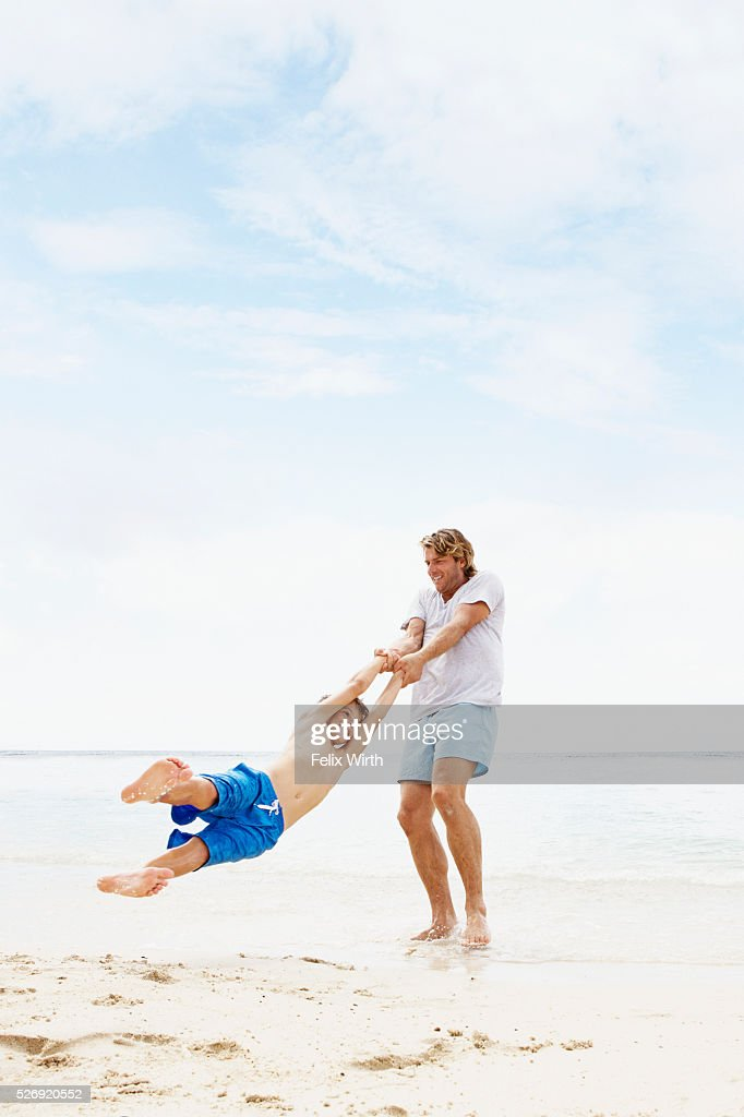 Father spinning his son (10-12) in air on beach : Foto stock