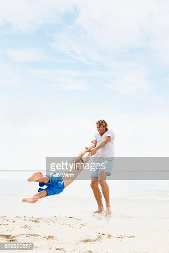 Father spinning his son (10-12) in air on beach : Stock Photo