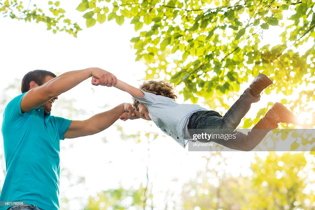 Father spinning his son in the nature and having fun.