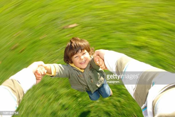 Father Spinning Son on Grass