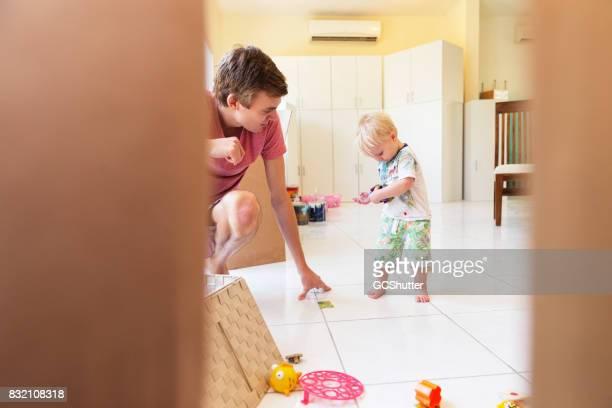Vater hocken nach unten um zu sehen, was sein Sohn in seinen Händen hält