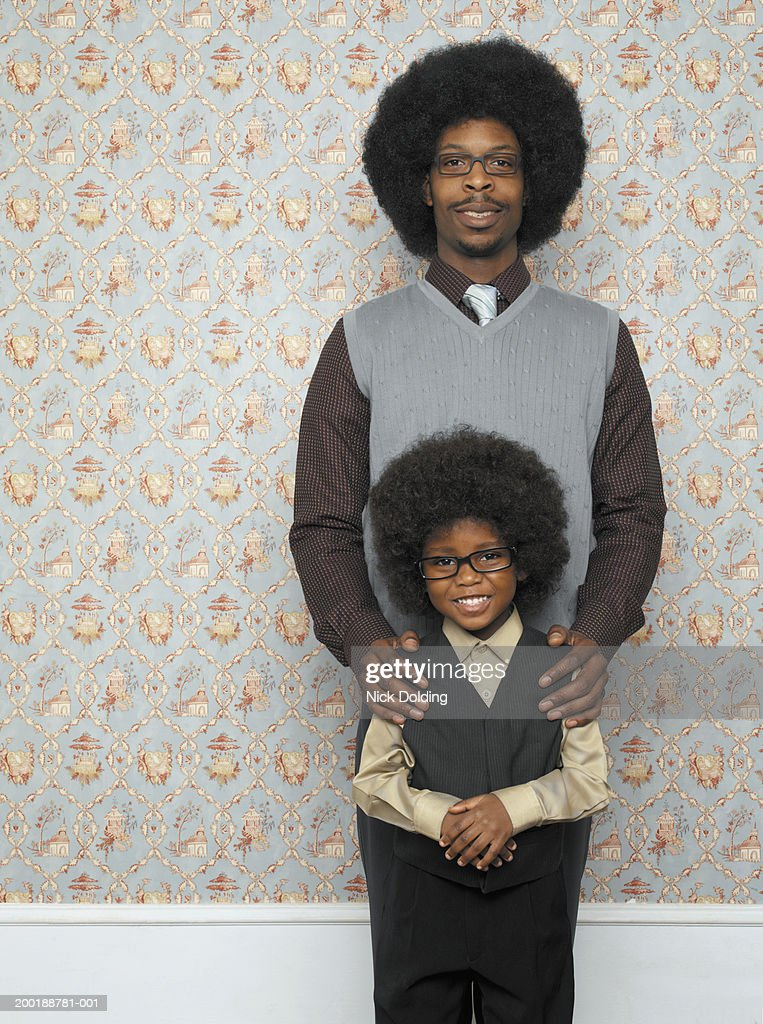 Father standing behind son (4-6) indoors, smiling, portrait
